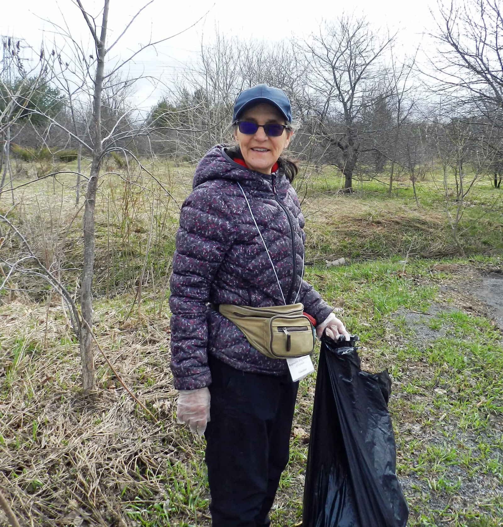 Betty Harris cleans up around the parking lot near the Shea Woods.